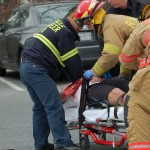 EMT workers gets the injuried pedestrian, Evan Hoppman onto the cart.