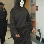 The grim reaper is followed by the police officer to the next victim's classroom.