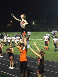 Senior cheerleaders Brendan Andrews and Mackailee Culotta perform a stunt for the fans and cheering to support the football players.