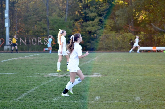 Freshman Charlotte Davis runs across the field.