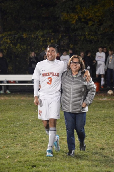 Senior Steve Cevallos walks the field with his mother.