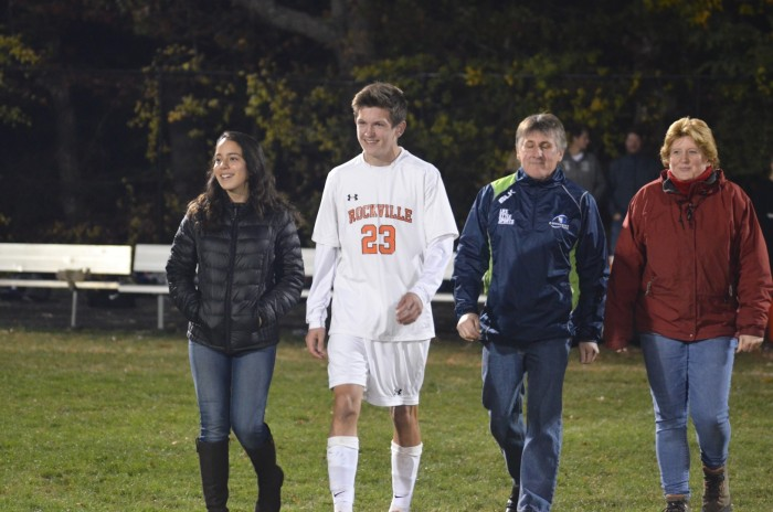 Senior Conor McGinley walks across the field with friends and family.