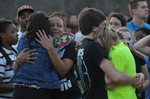 Senior Alexiana Bernard (left) and junior Jazmine Williams embrace during Michelle Miller's memorial as do senior Dominic Cicatelli (right) and junior Hayley Egart. Hundreds of community members attended the memorial to share their condolences and express support for the Miller family. --Sarah Huang, courtesy of the Yearbook