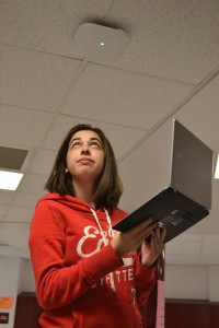 Junior Michaela Berger observes the white Wi-Fi router on a hallway ceiling. Berger of ten brings her laptop to school. --Elissa Britt