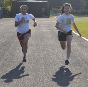 Sophomores Brianna Anthony and Emily Gee run along the track at off-season girls' basketball workouts in order stay in shape and prepare for upcoming tryouts starting Nov. 15.