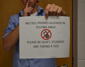 A student poses with a sign prohibiting technology in a testing room.
