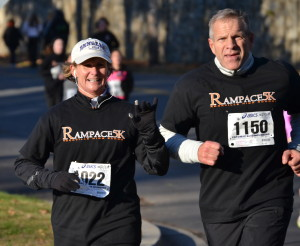 RHS Principal Billie-Jean Bensen and runner Don Marette race by. Bensen ranked 71 out of a total of 163 total runners that were ranked.
