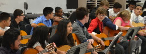 "Guitar students prepare their instruments for the concert. The students played together along with some individual performers such as freshman Riordan Caisse playing ""Hey There Delilah."" --Elissa Britt"