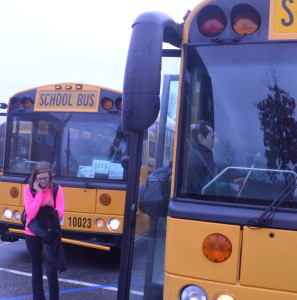A parked bus has its stop signs extended and flashing. Passing a stopped bus in Maryland warrants an expensive citation. --Adam Bensimhon