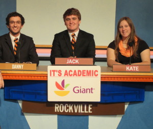 Seniors Danny Hoffman, captain Jack Berrigan and Kate Lipman compete at the podium during their quarterfinals in the It's Academic Playoffs Feb. 18. Competitions include trivia from many subjects. --Courtesy of It's Academic