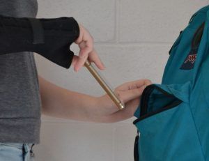 A student pulls a phone out of another student's backpack as a posed example of the alleged thefts of multiple electronics. Some devices are yet to be found and returned. --Mercy Fosah