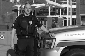 Corporal police officer Rick Halverson  stands next to his SUV outside the building. --Adam Bensimhon