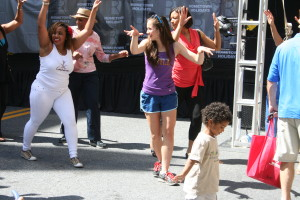Junior Erin Johnson dances with a Latino dance crew in the middle of Rockville Town Square at Hometown Holidays. She participated in a line dance. --Sarah Wagner