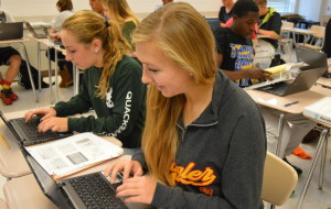 Senior Anna Walker (front) and junior Erin Moriarty (back) use the Chromebooks in their AP Psychology class with teacher Christine Zafonte. They used the laptops to finish an assignment. --Mercy Fosah