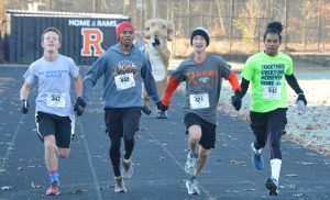Senior Billy Kirk, Miguel Suero Nolasco, Manuel Suero and junior Adam Sarsony (third from left) hold hands as they prepare to finish the race. They created a four-way-tie for first place, the first ever in Rampace history. --Meklit Bekele