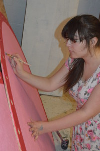 Senior Kelly Flynn paints set pieces for the spring musical,