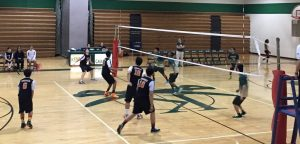 Sophomore outside hitter Doug Aubertin begins his approach as he is getting ready to hit sophomore setter Brandon Kim's high set, while Kennedy players begin to jump to try and block Aubertin's hit.