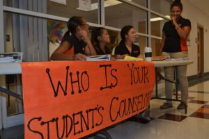 Student ambassadors assist parents in front of the counseling office.