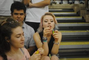(Left to right) Seniors Lyna Bentahar, Leo Blondel and Lena Bradley sit on the bleachers and blows bubbles before the start of the pep rally.