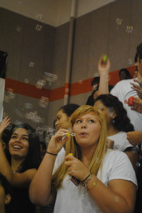 Senior Courtney Herzog blows bubbles during the pep rally.