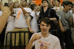 Senior Inferno leader, James Morey blows bubbles by the senior section of the pep rally.