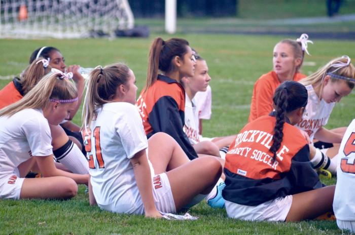 The girls varsity soccer team gathers to listen to their coach speak.
