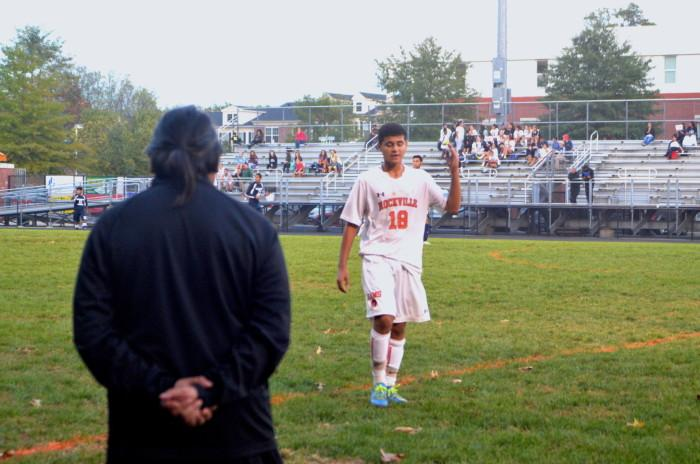 Junior Luis Aquino approaches his coach during the game.