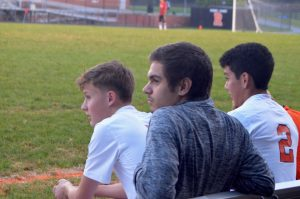(Left to Right) Seniors Robin Clarke, Samuel Mejia, and Ronaldo Reyes watch the game form the sidelines.