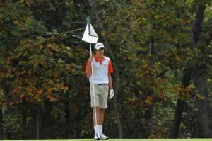 Freshman Cole Kirchner politely holds the flag while players from competing schools are putting.