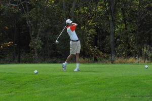 Freshman Cole Kirchner hits a line drive out onto the greens.