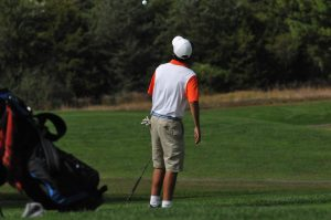 Junior Koby Kovacs playfully  tosses his ball in the air while waiting his turn.
