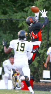 Senior Mickey Vangeison jumps over Richard Montgomery player to make the catch.