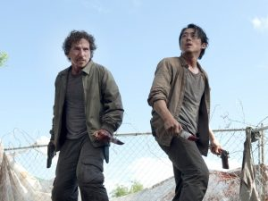 Nicholas (left) and Glenn (right) on top of a dumpster attempting to fend off a group of walkers. Courtesy of AMC.