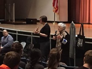 "Holocaust survivor Edith Lowy (right) speaks to RHS students Feb. 23. She is wearing a replica of the Star of David armband she was forced to wear in the Wieliczka ghetto. To her right are a replica of a concentration camp prisoner's outfit and a tote bag from the United States Holocaust Memorial Museum that reads ""Never Again."""